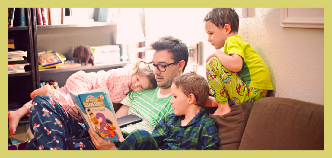 positive parenting: father reading to children
